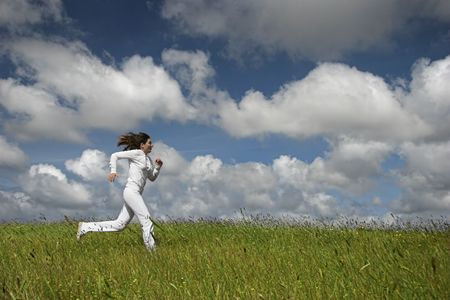 Beautiful woman running on a green meadow Stock Photo - 1320488