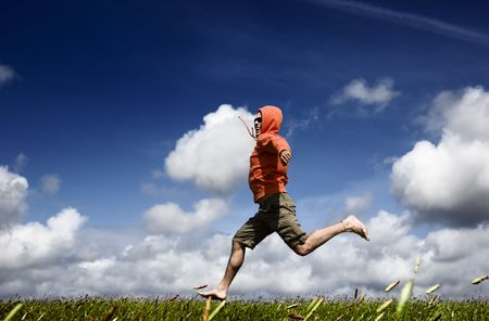 Man running and jumping on a green meadow Stock Photo - 1320475