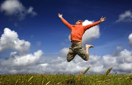 Man jumping on a green meadow with a beautiful cloudy sky Stock Photo - 1320489
