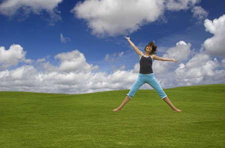 Beautiful happy woman jumping on a green field photo