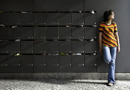 Young and beautiful woman thinking beside mailboxes photo