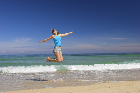 Beautiful young woman jumping on a beautiful beach Stock Photo - 1655596