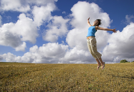 Beautiful woman jumping on a golden meadow