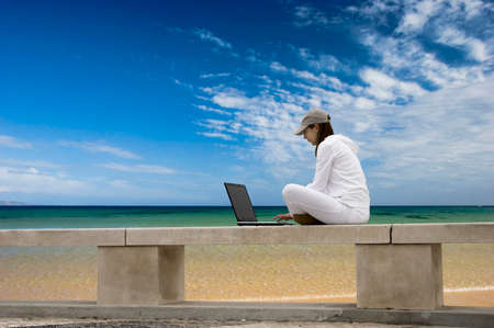 Woman working with a laptop sitting in a wall with a great view over a beautiful green meadow Stock Photo - 1684674