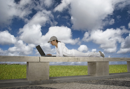 Woman working with a laptop sitting in a wall with a great view over a beautiful green meadow Stock Photo - 1684693