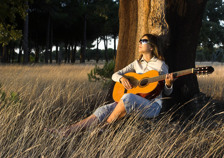 Woman playing her guitar at the sunset