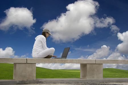 Woman working with a laptop sitting in a wall with a great view over a beautiful green meadow photo