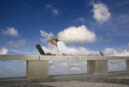 Woman working with a laptop sitting in a wall with a great view over a beautiful green meadow Stock Photo - 1728638