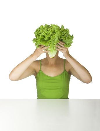 Woman in green holding a lettuce in front of the face photo