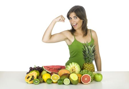 Beautiful and strong healthy woman with a lot of fruits in front of her