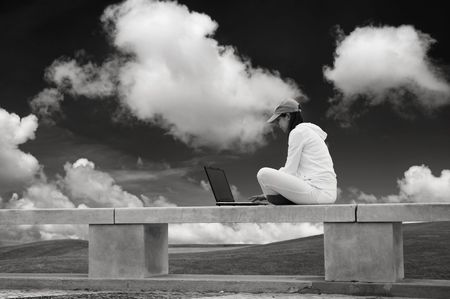 Woman working with a laptop sitting in a wall with a great view over a beautiful green meadow Stock Photo - 1747421