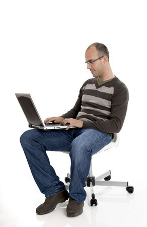 Buziness man seated on chair and working on a laptop photo