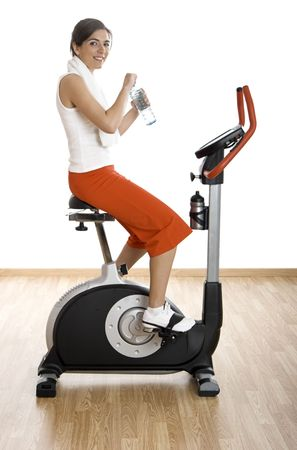 Young woman training on exercise bike at the gym and drinking water photo