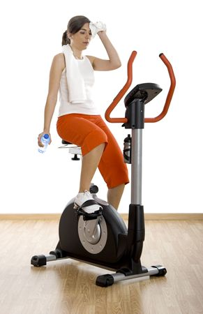 Young woman tired of training on exercise bike at the gym  photo