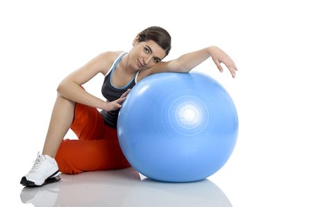 Beautiful young woman relaxinx with a core ball isolated on white photo