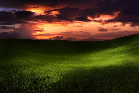 Beautiful green meadow with sunset clouds photo