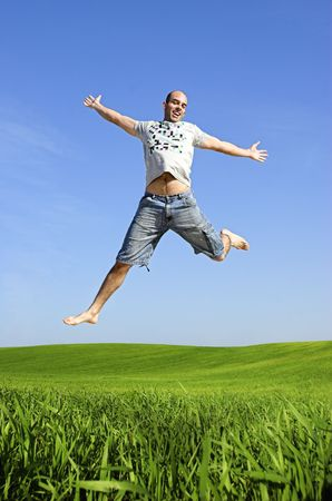 Man making a big jump on a beautiful green meadow photo