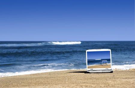 fiestas electronicas: Abrir port�til en una hermosa playa con un gran cielo azul  Foto de archivo