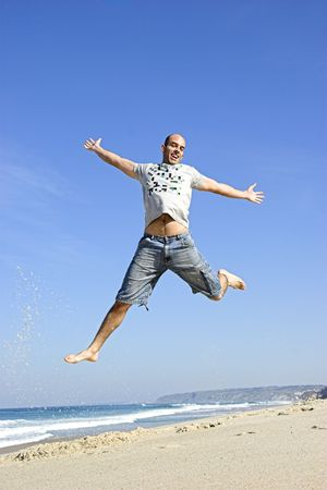 Man jumping on the beach and having fun photo
