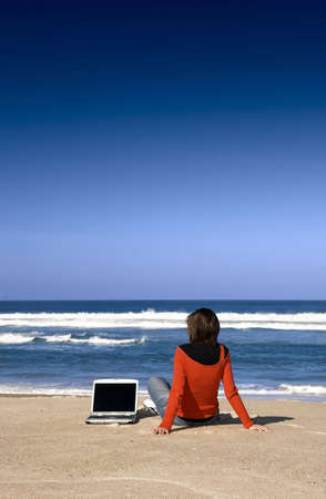 laptop outside: Woman working with a laptop on the beach Stock Photo