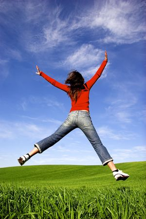 Woman making a big jump on a beautiful green meadow photo