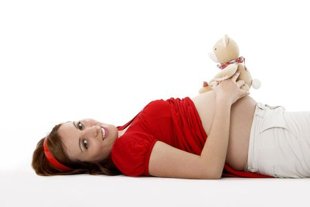 Beautiful pregnant woman with a teddy bear photo