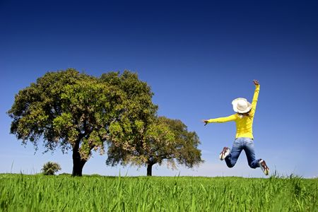 Haapy woman jumping on a beautiful green meadow with trees photo
