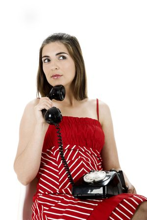 Young beautiful woman seated on a chair making a call with an hold vintage phone photo