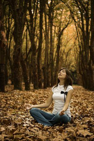 Beautiful woman making Yoga the beautiful Autumn Park Stock Photo