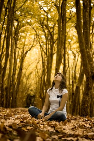 Beautiful woman seated on the ground in a beautiful Autumn Park photo