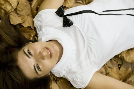 Young beautiful woman lying in the autumn park photo
