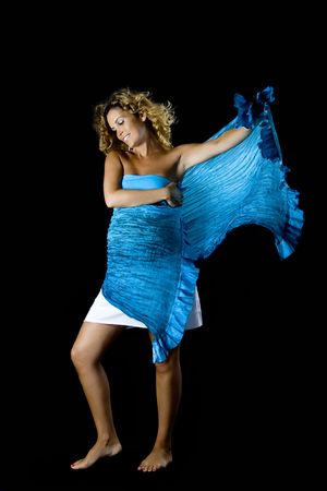 Beautiful pregnant woman posing with a blue handkerchief isolated on a black background photo