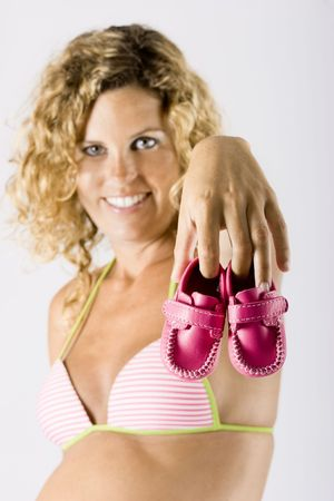 Beautiful pregnant woman holding small baby shoes - selective focus photo