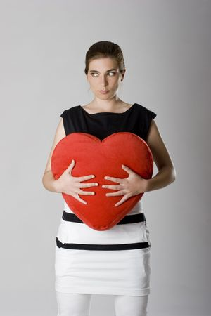 Sad woman holding a heart - Concept about a sad valentine day photo