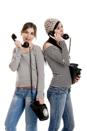 Two young women talking with old telephones - Isolated on white