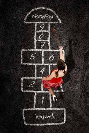 Beautiful young woman playing hopscotch with a red dress    photo