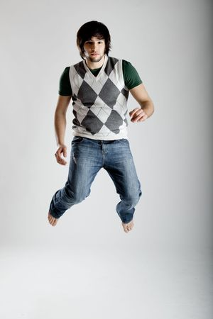 Young modern man jumping over a white background Stock Photo - 4748784