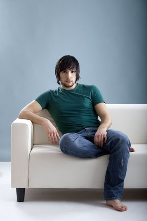 Good-looking young man at home seated on the couch photo