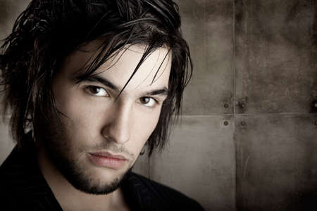 Good looking  young man with modern HairStyle over a grunge wall background