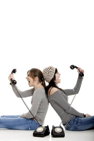 Two young women talking with old telephones - Isolated on white Stock Photo - 4851331