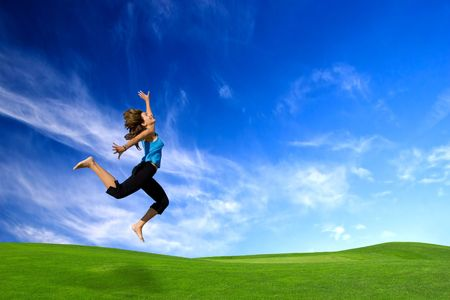 Beautiful athletic woman jumping on a green meadow photo