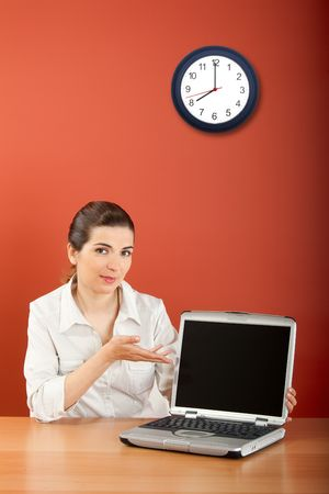 Businesswoman sitting in office with a laptop showing something  photo