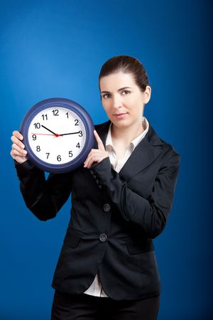 corporate waste: Beautiful young business woman olding a clock over a blue background