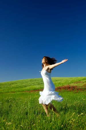 Beautiful happy young woman dancing on the field Stock Photo - 4980347