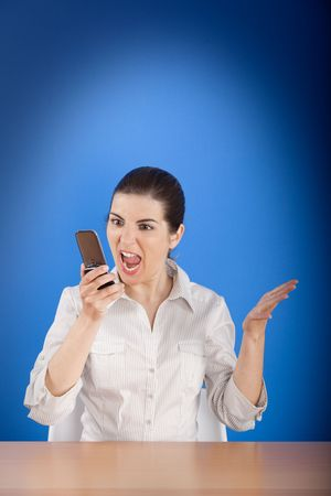 Angry young woman calling by cellular phone. photo
