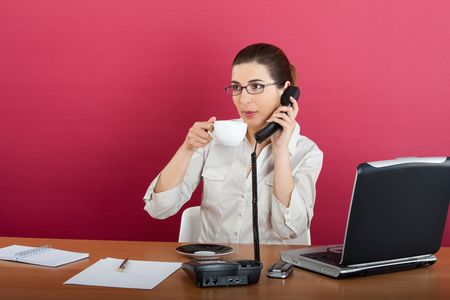Portrait of a young business woman speaking on the phone and drinking a coffee photo