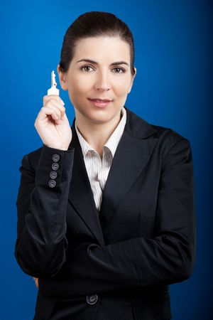 Beautiful young business woman olding keys over a blue background photo