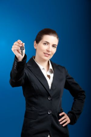 Beautiful young businesswoman olding keys - focus is on the keys photo