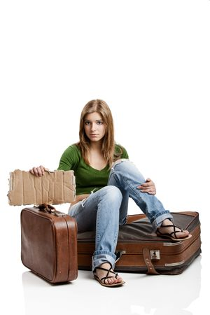 Beautiful young woman seated on the old suitcases holding a card tablet photo