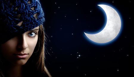 Portrait of a beautiful and young woman at night with a artifical moon on the background Stock Photo - 5036095